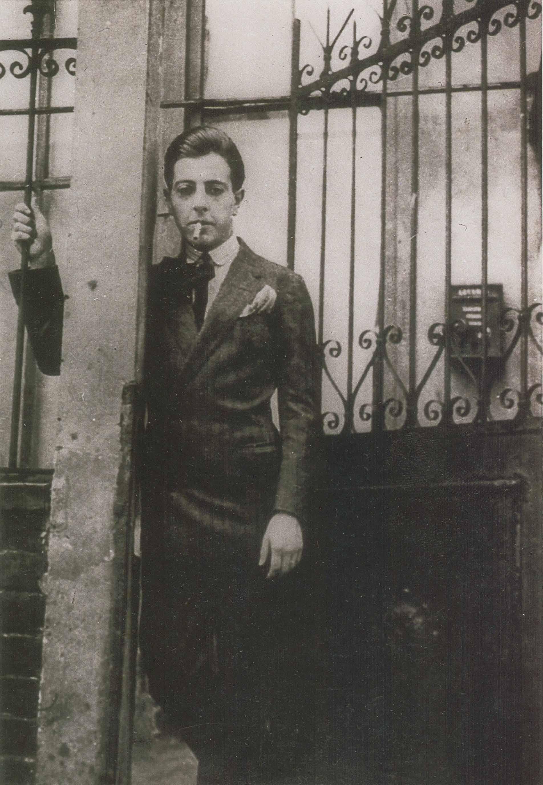 Jacques Prévert posant devant la grille de la rue du Château D.R.